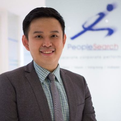 PeopleSearch consultant Tan Kok Pin standing in front of PeopleSearch signboard