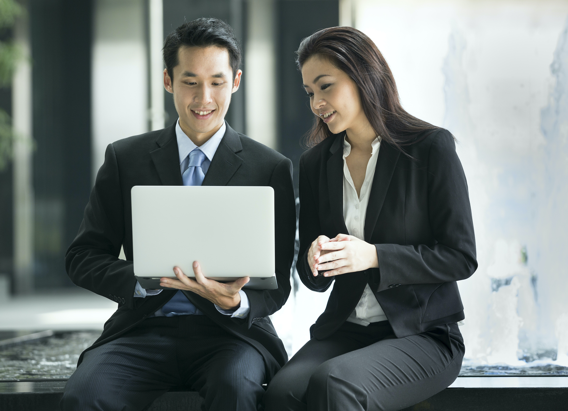 Asian male jobseeker and Asian female headhunter looking at laptop screen together