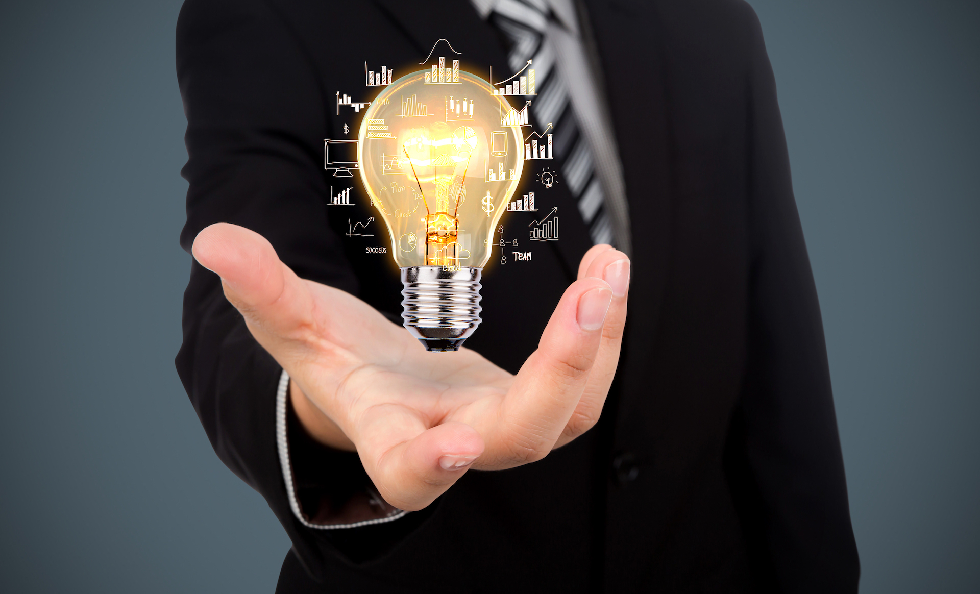 Man in black business suit holding a light bulb in his outstretched hand