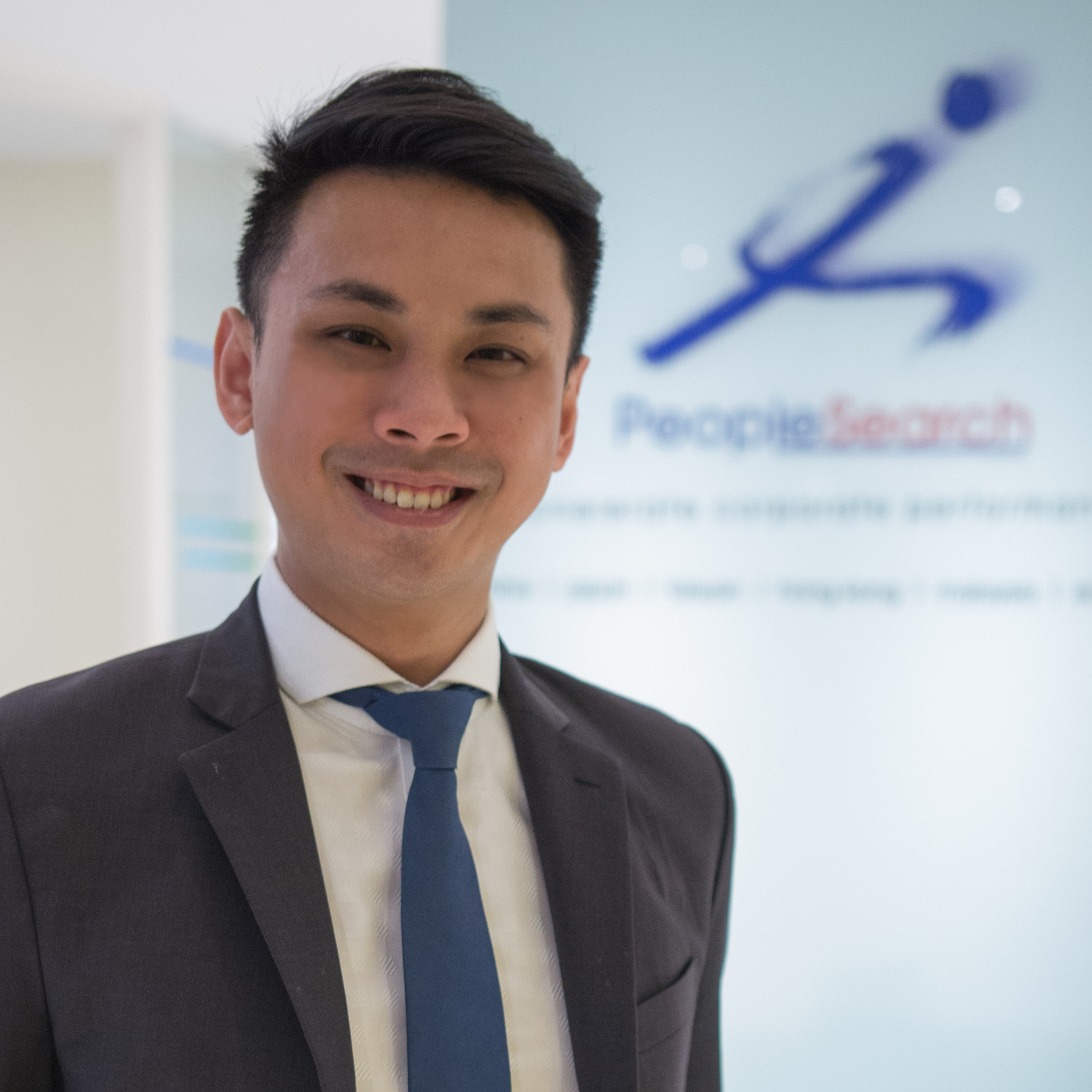 Asian man in dark grey suit and blue tie smiling into the camera