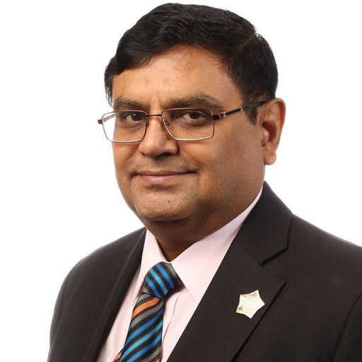 South Asian man in brown suit, colourful striped tie and glasses
