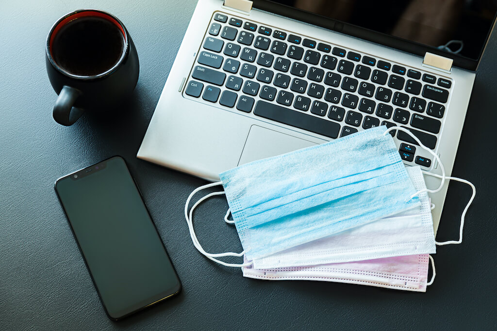 Surgical face masks on a laptop keyboard, coffee cup, mobile phone on desk