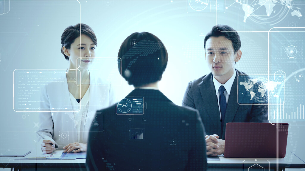 Asian man and woman in business attire interviewing a woman job applicant in a dark suit
