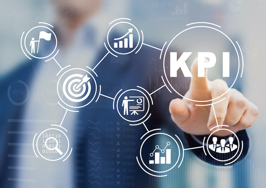 Professional in a blue suit pointing at KPI on a screen