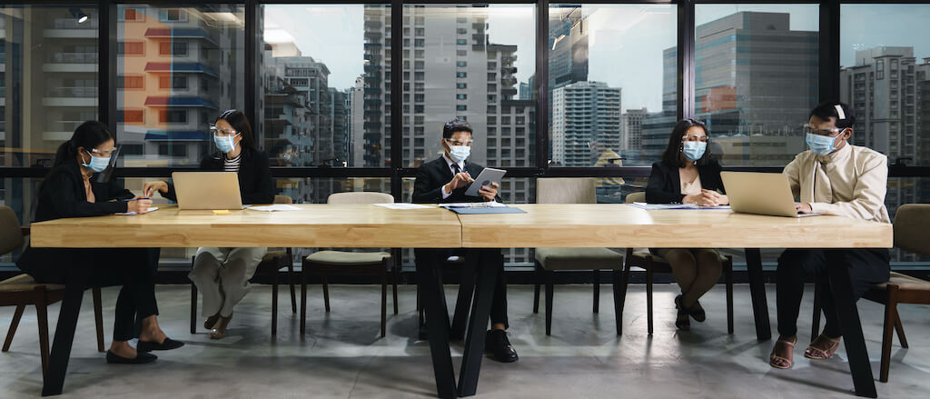 Men and women in business suits wearing face masks and working in the office