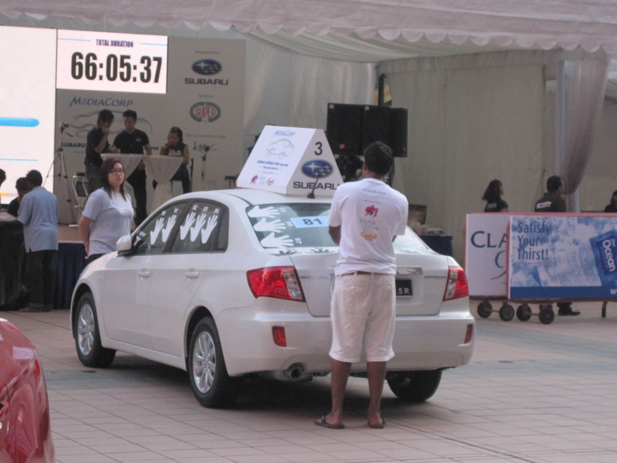 Man in white t-shirt and bermudas standing with his palm on a white car