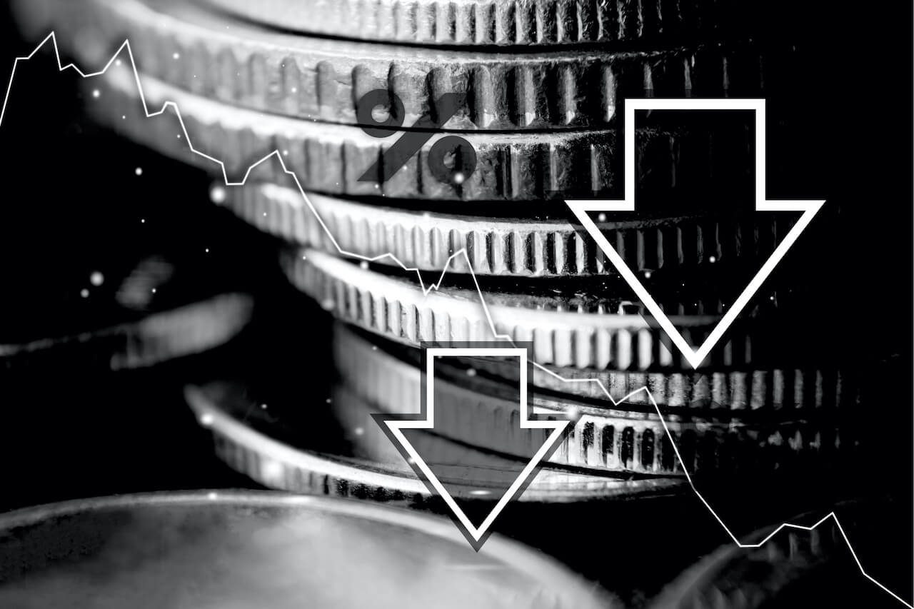 Coins in the background with symbol for percentage and arrows pointing downwards in the foreground.