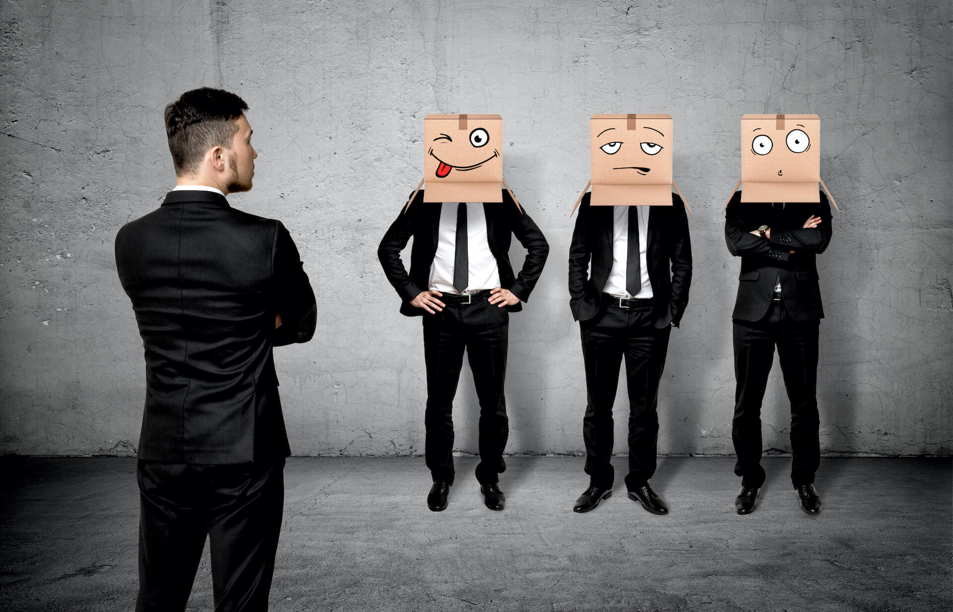 Man in business suit looking at three other men in business suits with funny-face paper bags over their heads in a room with concrete walls