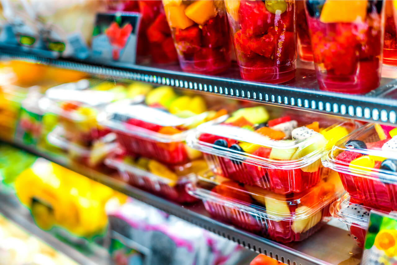 Watermelon, strawberries, mango and other fruits in plastic packaging on a supermarket shelf