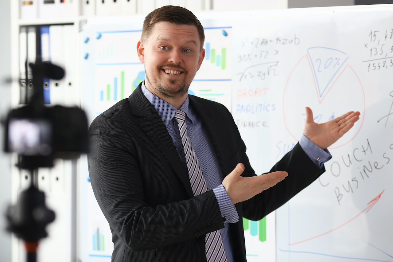 Executive in a suit making a presentation in front of a whiteboard while being filmed on a camera
