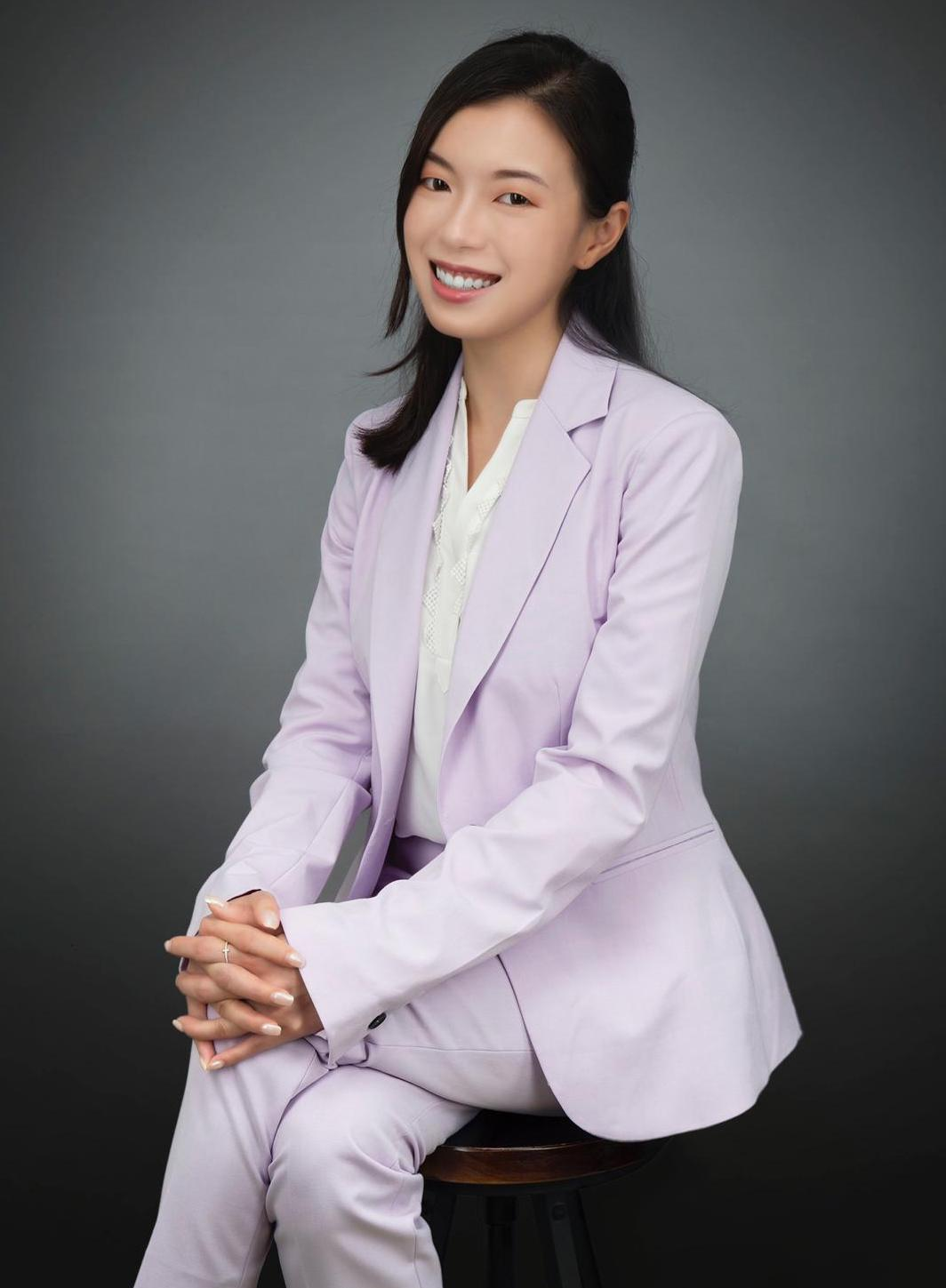 Asian woman in lavender business suit sitting on a chair