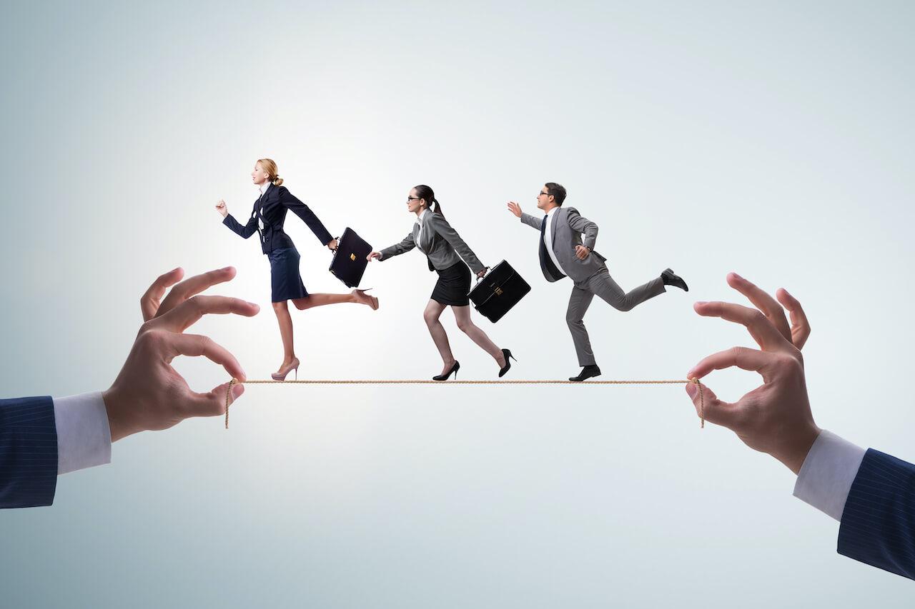 Male and female executives in business suits walking on a tightrope