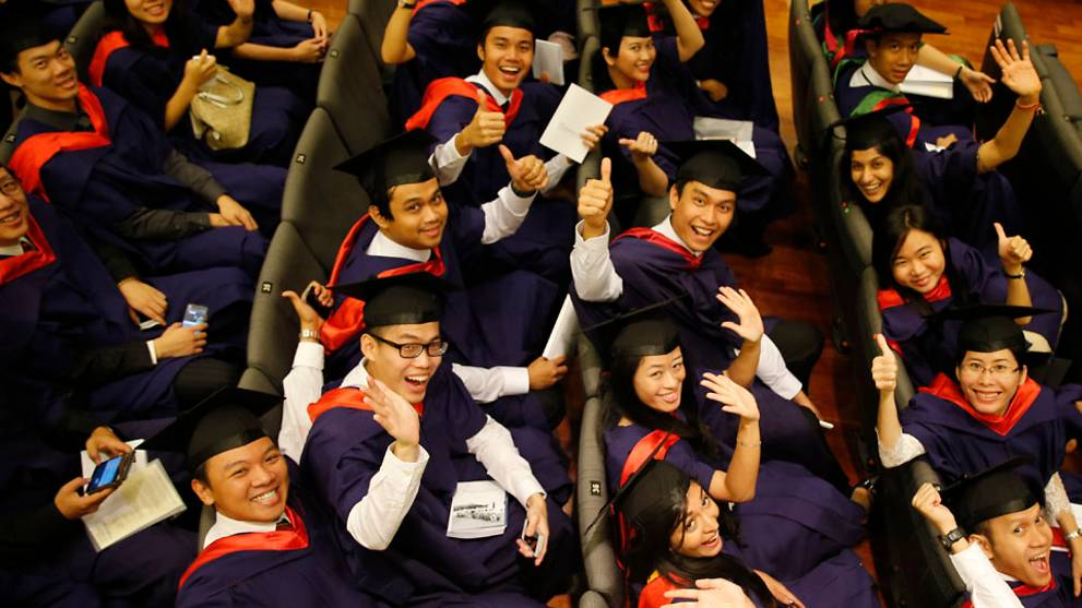 Young people in university graduation gowns seated and waving at camera