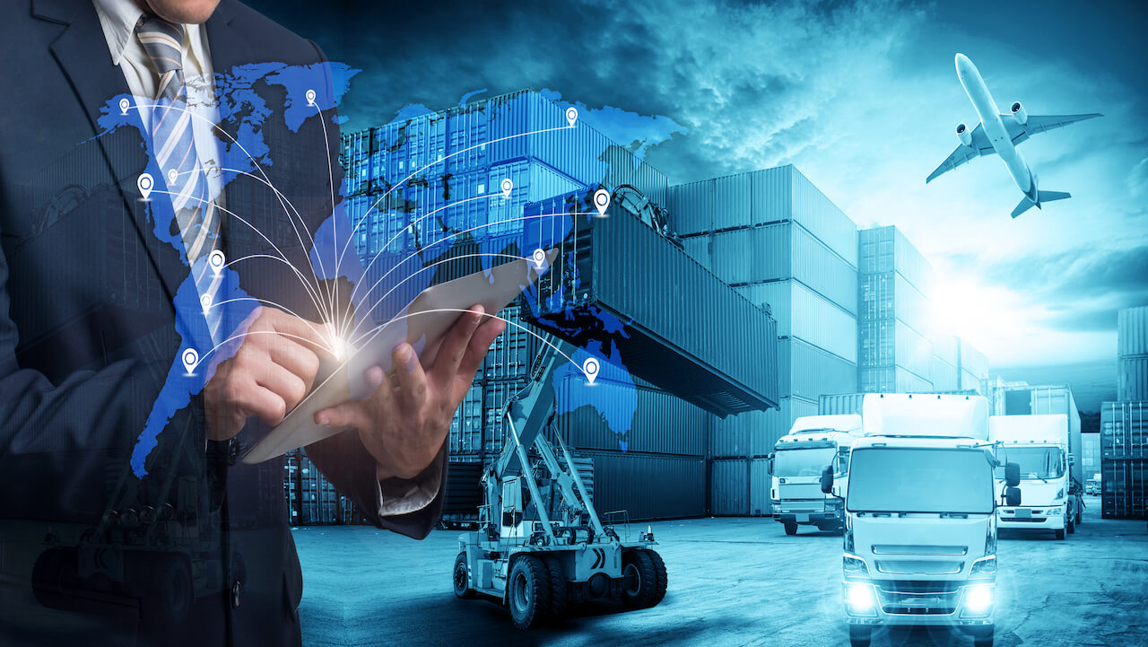 Man in suit with electronic pad standing against a supply chain backdrop with world map in the foreground