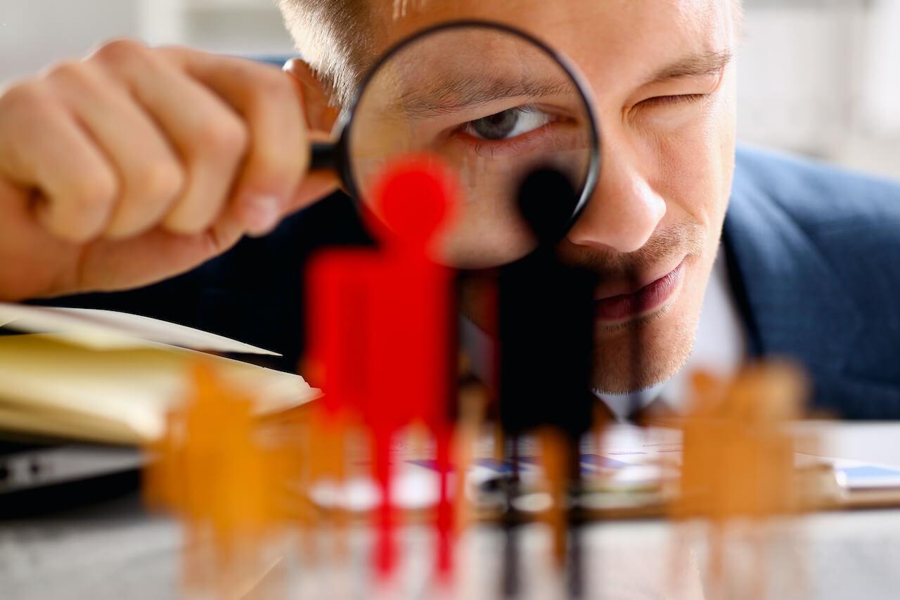 Man looking through magnifying glass examining job candidates