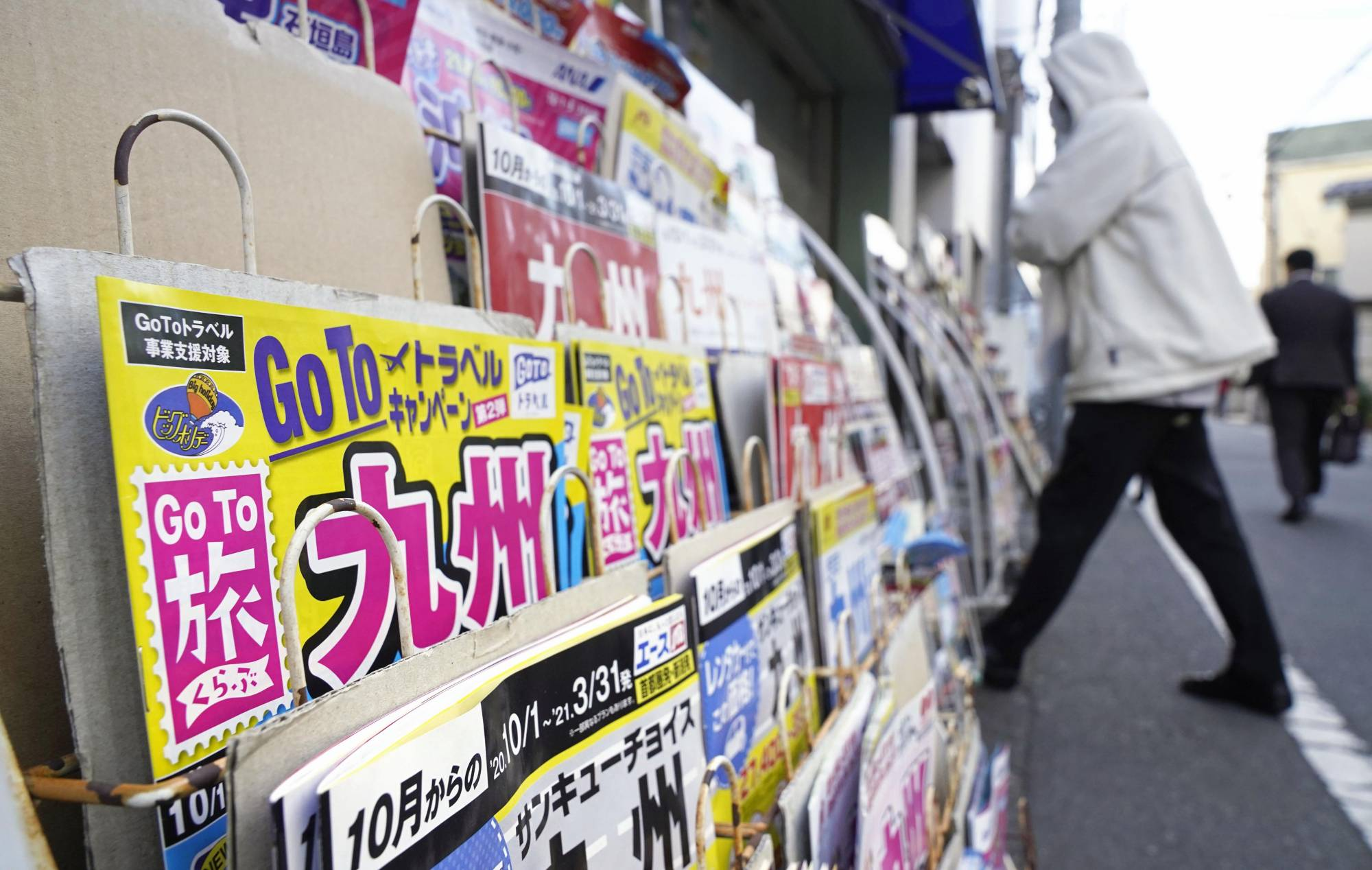 News stand in Japan with Japan's hospitality industry Go To Travel campaign on magazine cover